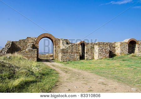 Ruins of an ancient town and path through arced gate