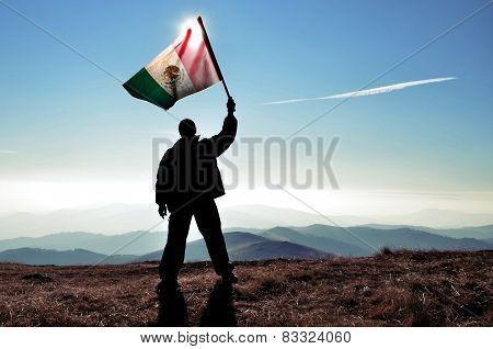 Men waving Mexican flag on a mountain top
