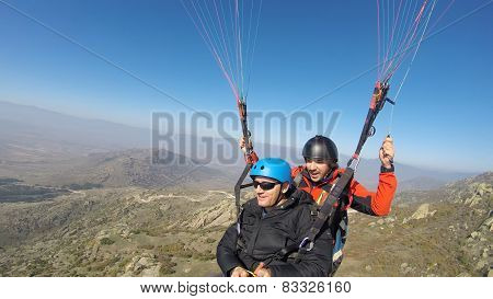 Man and pilot paragliding above the mountain