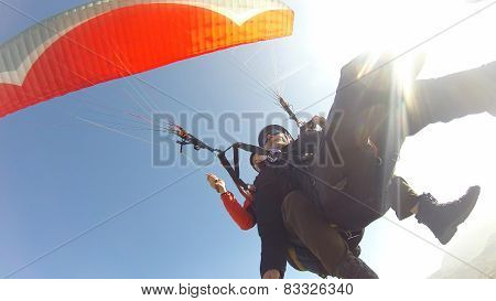 Paragliding against bright sun and blue sky