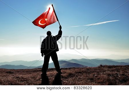 Man waving Turkish flag on mountain