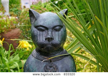 poster of Dramatic cat sulpture placed in the garden.