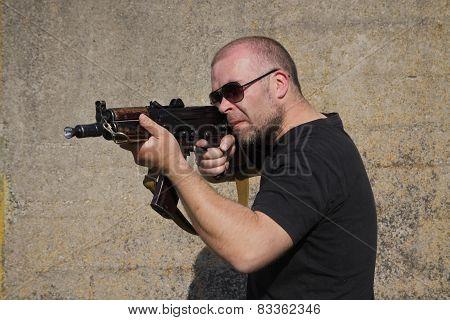 Man with glasses is holding Kalashnikov rifle. poster