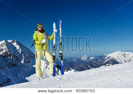 Young woman in mask stands and holds ski, poles