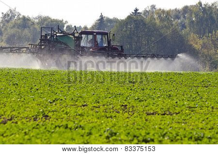 Tractor spray fertilize with insecticide herbicide chemicals in agriculture field and evening sunlight poster