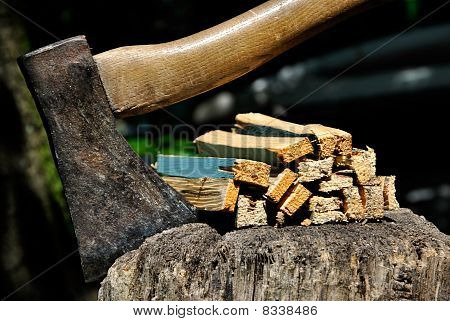 Old Axe Stuck In A Chopping Block With Splinters Closeup