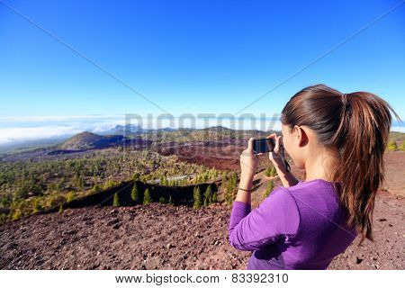 Hiker taking landscape picture on top of mountain. Beautiful nature on the volcano Teide, Tenerife, Canary islands with girl tourist using smartphone to take photos.