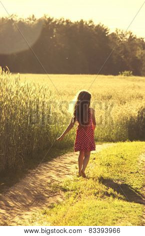 Beauty Girl Outdoors enjoying nature. Beautiful little girl in red dress running on the Spring Field