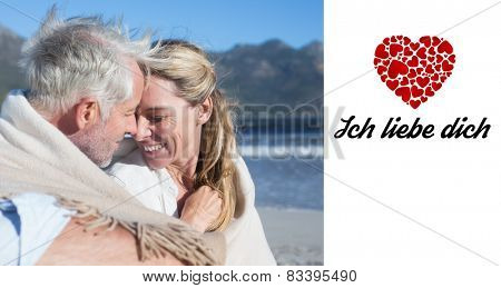 Smiling couple sitting on the beach under blanket against ich liebe dich