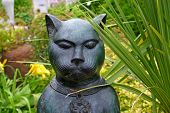 Dramatic cat sulpture placed in the garden. poster