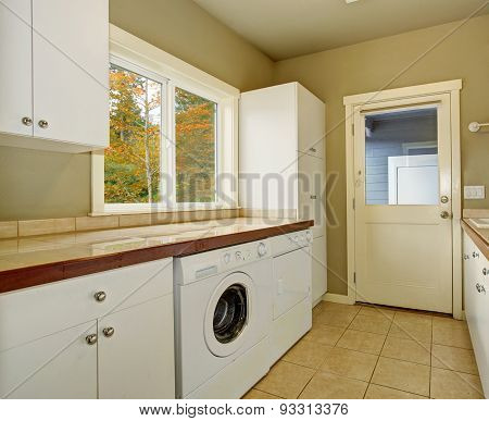 Laundry Room With Tile Counters And Sink.