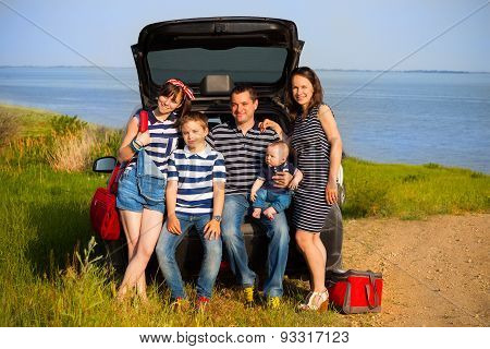 Family Of Five Having Fun On The Beach Going On Summer Vacation