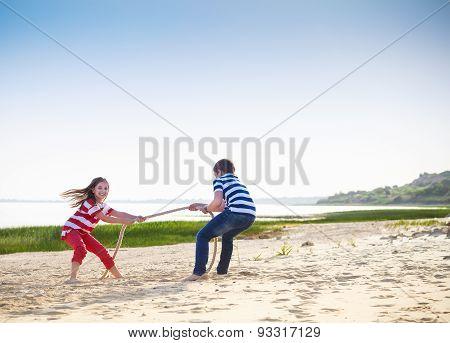 Tug Of War - Boy And Girl Playing On The Beach