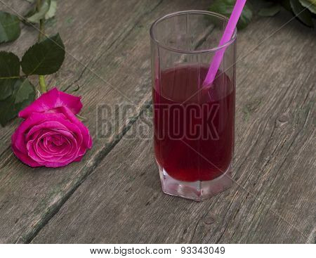 Glass Of Red Drink With A Tubule Nearby A Rose