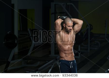 Muscular Young Man Doing Heavy Weight Exercise For Triceps In Gym poster