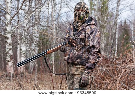 Hunter In The Camouflage With Gun
