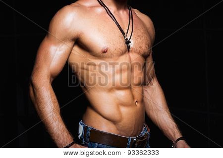 Muscular and sexy torso of young sporty man in jeans with perfect abs,  chest, bicep.