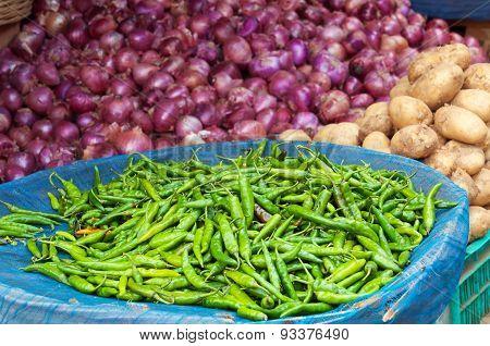 Pile of fresh green chili peppers onions potatoes on the street market. Bangalore. Karnataka. India poster