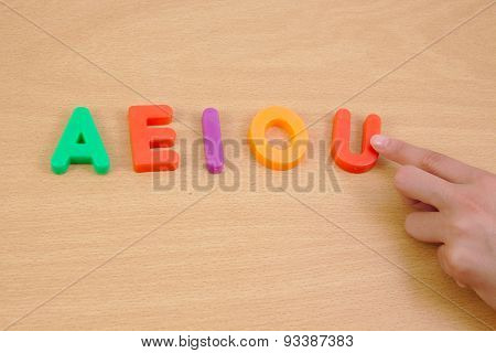 Letters a e i o u and child hand. School concept