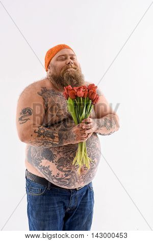 Happy fat man is holding bouquet of tulips and smiling. He is standing and smelling it. His eyes are closed with enjoyment. Isolated