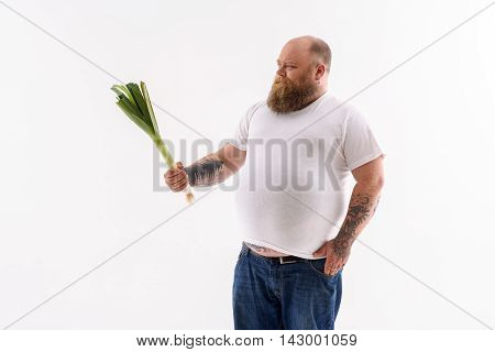 I do not want to eat it. Fat bearded man is standing and holding leek. He is looking at vegetables with hesitation. Isolated