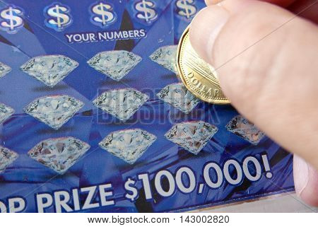 Coquitlam BC Canada - June 04, 2015 : Woman scratching lottery ticket. The British Columbia Lottery Corporation has provided government sanctioned lottery games in British Columbia since 1985.