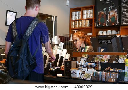 Coquitlam, BC, Canada - July 29, 2016 : Close up man buying coffee and paying by credit card inside Starbucks store