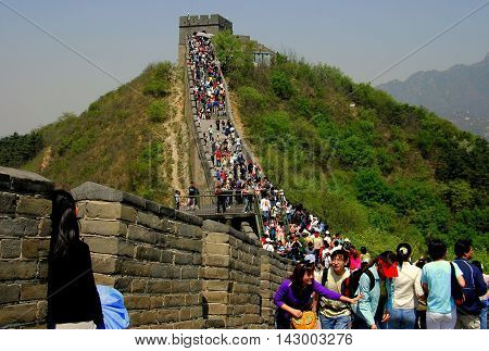 Badaling China - May 1. 2005: Throngs of visitors crowd the crenelated ramparts below a watctower at the Great Wall of China