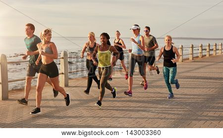 Group of runners running on urban street by the seaside. Healthy young people training together outdoors. poster