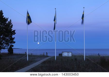 BALTIC SEA, SWEDEN ON JULY 21. View of an entry to a beach on July 21, 2016 by the Baltic Sea, Sweden. Billboard, standards and a few unidentified people. Nightfall. Editorial use.