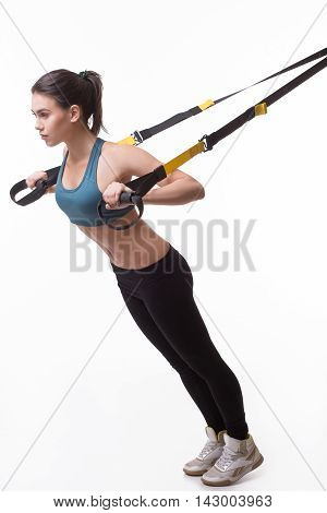 Upper body excercise concept. Image of beautiful woman exercising with suspension straps in studio. Lady posing in full length. TRX concept isolated on white background.
