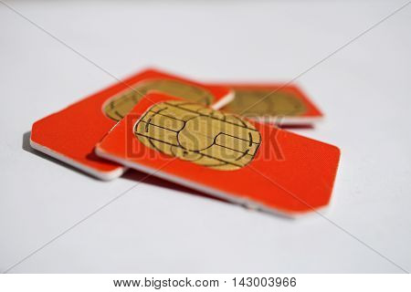 Isolated group of four red SIM cards used in the mobile phones (cell phone devices) with a focus on their golden micro chip