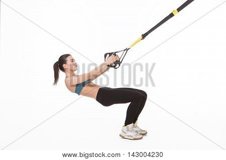 Upper body excercise concept. Pretty lady training with suspension trainer sling isolated on white background. Beautiful fitness trainer or coach showing her strong body with muscles.