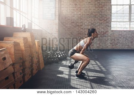 Tough Young Woman Exercising With Kettle Bell At Gym