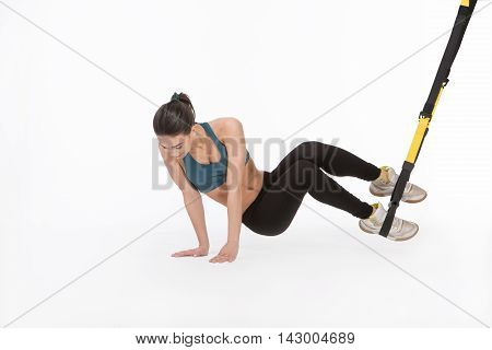 Beautiful lady training with suspension trainer sling or suspension straps. Core body excercise concept. Lady posing for photographer in studio.