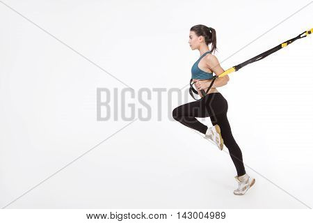 TRX concept. Beautiful lady exercising her muscles with help of suspension trainer sling or suspension straps isolated on white background.