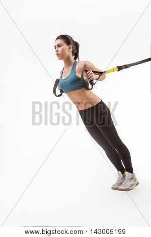 Low view of beautiful young lady posing for photographer while training suspension trainer sling. Lady exercising upper body on TRX in studio.