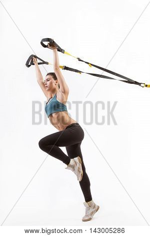 Low view of beautiful young woman training with suspension trainer sling or suspension straps isolated on white background in studio. Upper body excercise concept on TRX.