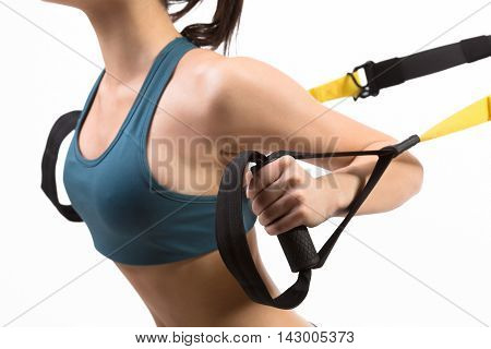 Closeup picture of young sports lady training upper body on suspension trainer sling or suspension straps in studio. Lady exercising on TRX isolated on white.