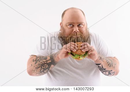 Hungry fat man is eating sandwich with greed. He is standing and looking aside with fear. Isolated