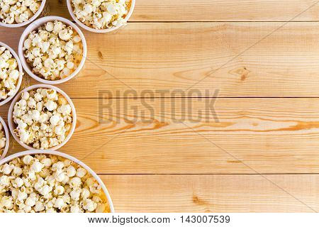 Movies background with various sized full popcorn bowls on table from top down perspective