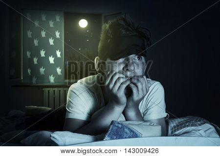 scared and sleepless boy chewing fingernails at bedroom in front of shiny moon