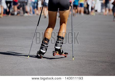 feet young female athlete in ski-roller rides on asphalt