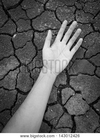 black and white man hand on crack soil