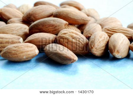 Pile Of Almonds Against A Blue Background #1