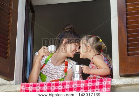 Lovely touching with their noses mother and two years old daughter are holding traditional Italian coffee set of white cup and metal moka pot