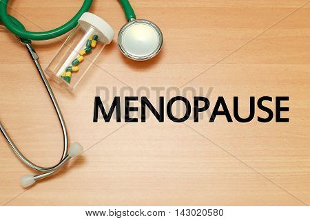 Medical concept - Stethoscope and pills on wood with Menopause word