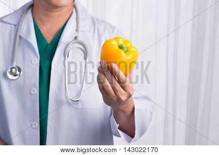Nurse or male doctor giving bell pepper smiling. Health care concept isolated on white background.