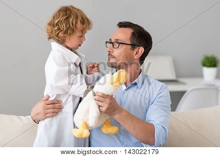Here is a new patient. Serious man giving to his little cute doctor in a hospital gown a toy while looking at him