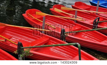 red and blue boat with oars, on the quay